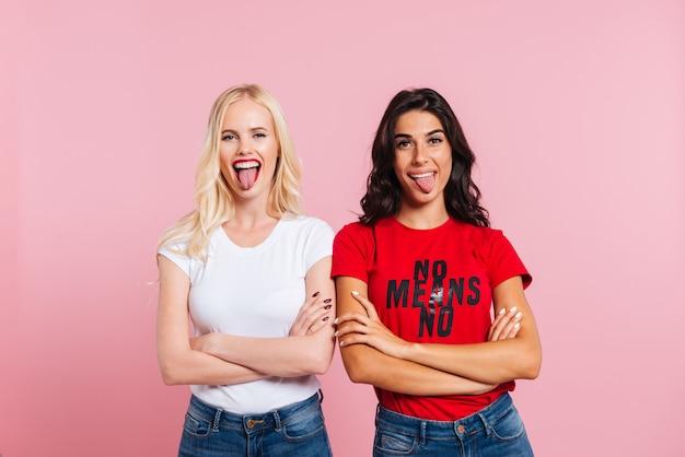 Jonge grappige vrouwelijke vrienden die geïsoleerde tong tonen