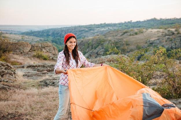 Jonge gril verzamelt tent op berg