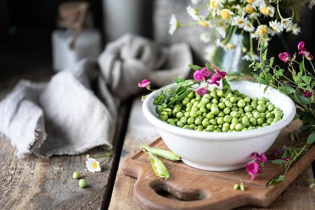 Jonge groene erwten in witte kom op houten achtergrond. erwtenbloemen en madeliefjebloemen op de lijst.