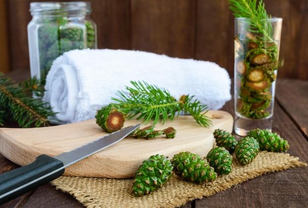 Jonge groene fir kegels op de houten achtergrond. hakmessenkegels voor het maken van medicinale infusie.