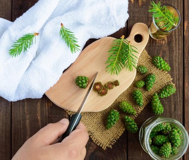 Jonge groene fir kegels op de houten achtergrond. handmaalt messenkegels voor het maken van medische infusie. bovenaanzicht