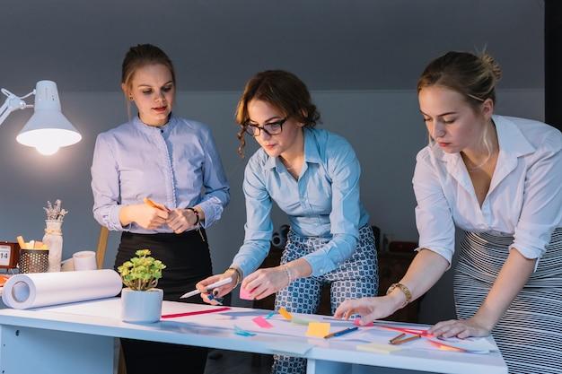Jonge groep creatieve onderneemster die aan bedrijfsproject op het kantoor werken