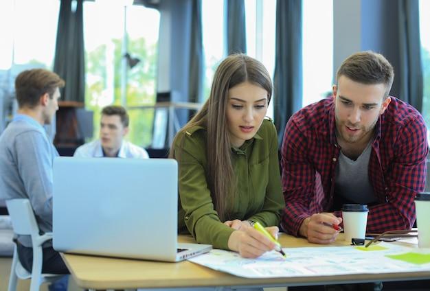 Jonge groep mensen die hun werk op laptop doen.