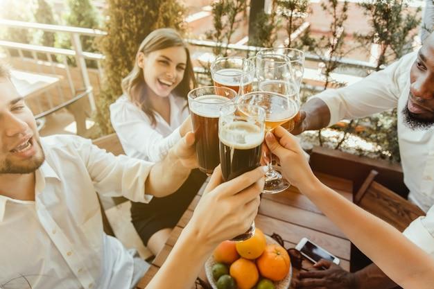 Jonge groep vrienden bier drinken, plezier maken, lachen en samen vieren. vrouwen en mannen met bierglazen in zonnige dag. oktoberfest, vriendschap, saamhorigheid, geluk, zomerconcept.