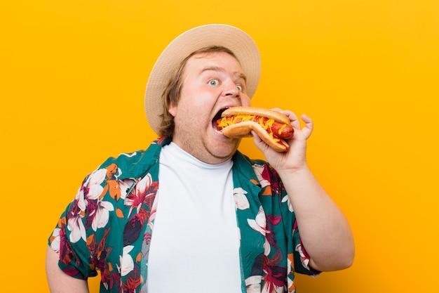 Jonge groot formaat man met een hotdog tegen platte muur