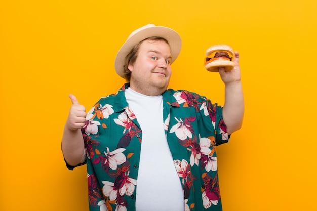Jonge groot formaat man met een kaas hamburger vlakke muur