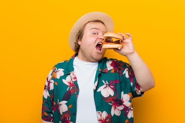 Jonge groot formaat man met een kaasburger tegen vlakke muur