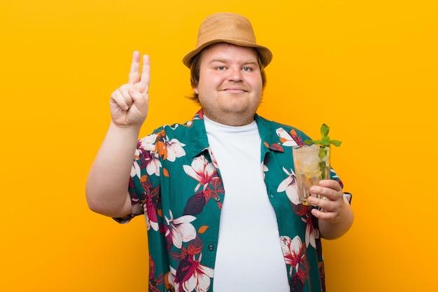 Jonge groot formaat man met een mojito drankje tegen vlakke muur