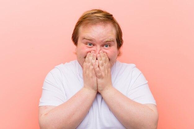 Jonge groot formaat man op zoek gelukkig, vrolijk, gelukkig en verrast bedekkende mond met beide handen over roze muur