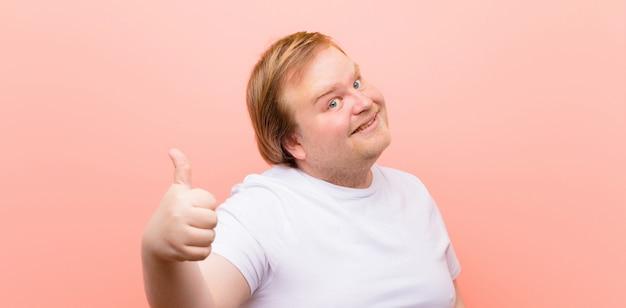 Jonge groot formaat man voelt zich trots, zorgeloos, zelfverzekerd en gelukkig, positief glimlachend met duimen tegen roze muur