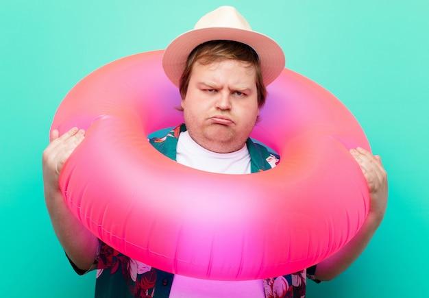 Jonge grote man met een opblaasbare donut op een vlakke muur