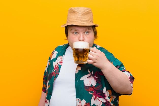 Jonge grote man met een pint bier tegen een vlakke muur