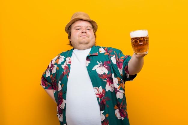 Jonge grote man met een pint bier vlakke muur