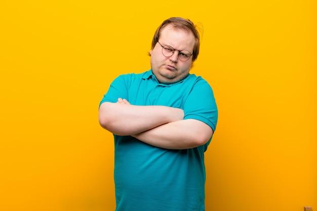 Jonge grote man voelt zich ontstemd en teleurgesteld, kijkt ernstig, geïrriteerd en boos met gekruiste armen op oranje muur