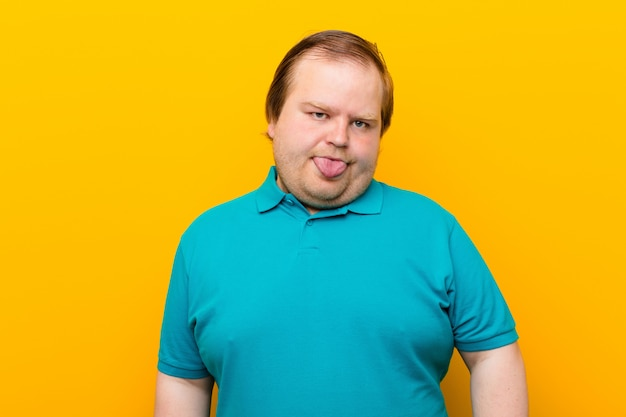 Jonge grote man voelt zich walgend en geïrriteerd, steekt zijn tong uit, houdt niet van iets smerigs en vies op de oranje muur