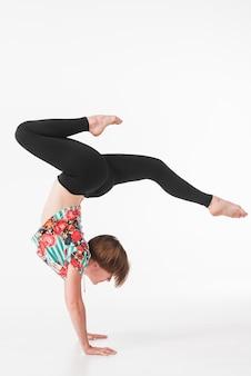 Jonge gymnastiek- vrouw dansen op witte achtergrond