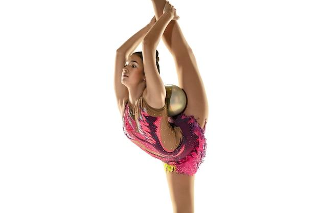 Jonge gymnastiekatleet die op witte studiomuur wordt geïsoleerd