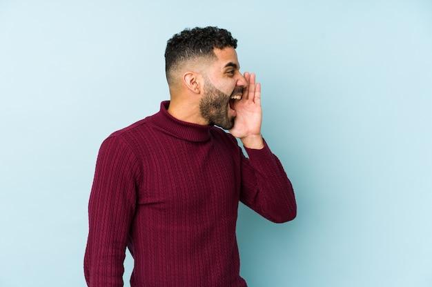 Jonge halfbloed arabische man geïsoleerd schreeuwen en palm in de buurt van geopende mond houden.