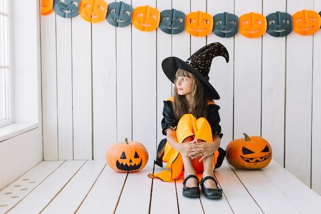 Jonge halloween-heks die bij venster meespelen