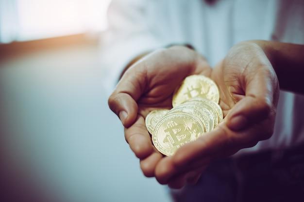 Jonge hand die veel gouden bitcoin en zilver bitcoin in twee handen.