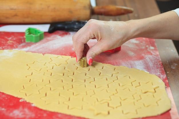 Jonge handen die gemberdeeg snijden bij moderne keuken