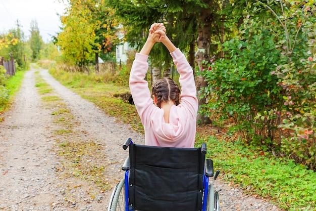 Jonge handicap vrouw in rolstoel op weg in ziekenhuis park