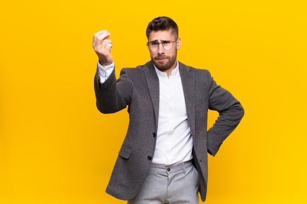 Jonge handosme man die capice of geldgebaar maakt en je vertelt om je schulden te betalen! over kleurenmuur