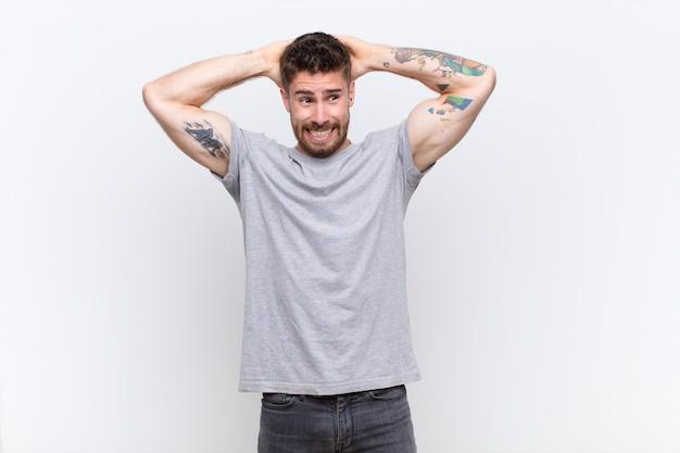 Jonge handosme man voelt zich gestrest, bezorgd, angstig of bang, met handen op het hoofd, in paniek bij vergissing over de muur
