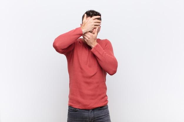 Jonge handosmeman die gezicht behandelt met beide handen die nee zeggen tegen de camera! afbeeldingen weigeren of foto's verbieden over een kleurenmuur
