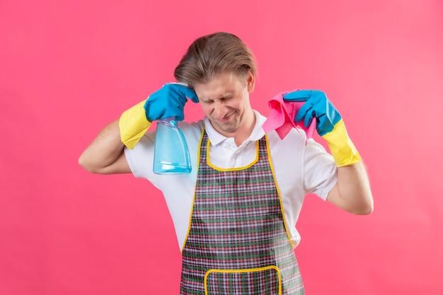 Jonge hansdome-man die een schort en rubberen handschoenen draagt die schoonmaakspray en een tapijt houdt, kijkt gestrest en nerveus