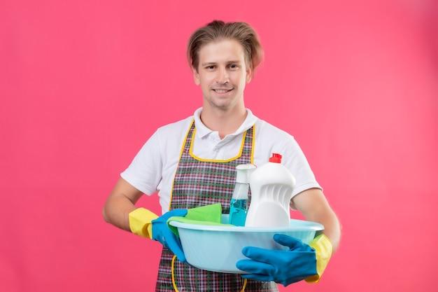Jonge hansdome-man die schort en rubberhandschoenen draagt die bassin met schoonmakende hulpmiddelen met zelfverzekerde glimlach op gezicht over roze muur houdt