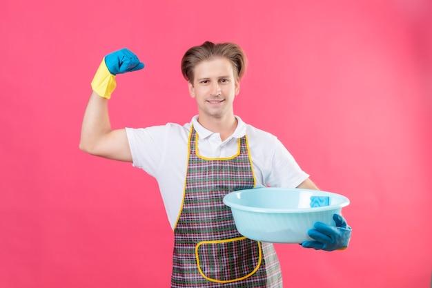 Jonge hansdome-man die schort en rubberhandschoenen draagt die bekken met schoonmakende hulpmiddelen houdt die vuist opheft die zijn succes met zelfverzekerde glimlach op gezicht verheugt dat zich over roze muur bevindt