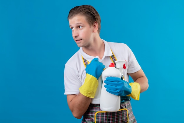 Jonge hansdome-man die schort en rubberhandschoenen draagt die fles met schoonmaakmiddelen houdt die opzij kijkt met zelfverzekerde glimlach op gezicht dat zich over blauwe muur bevindt