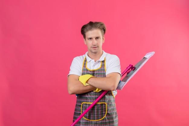 Jonge hansdome-man die schort en rubberhandschoenen draagt die zwabber met ernstige zelfverzekerde uitdrukking op gezicht houdt die zich met gekruiste wapens over roze muur bevindt