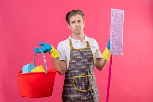 Jonge hansdome-mens die schort en rubberhandschoenen draagt die emmer met schoonmakende hulpmiddelen en dweil houdt
