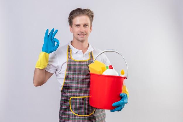 Jonge hansdome-mens die schort en rubberhandschoenen draagt die emmer met schoonmakende hulpmiddelen houden