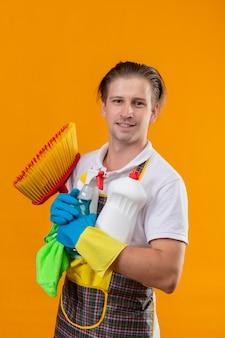 Jonge hansdome-mens die schort en rubberhandschoenen draagt die schoonmakende hulpmiddelen houden