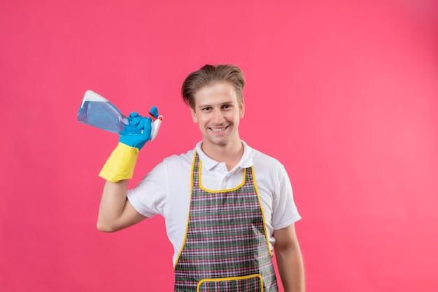 Jonge hansdome-mens die schort en rubberhandschoenen draagt die schoonmakende nevel houdt