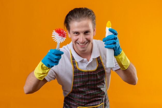 Jonge hansdome-mens die schort en rubberhandschoenen draagt die schrobborstel en fles met schoonmakende levering houden