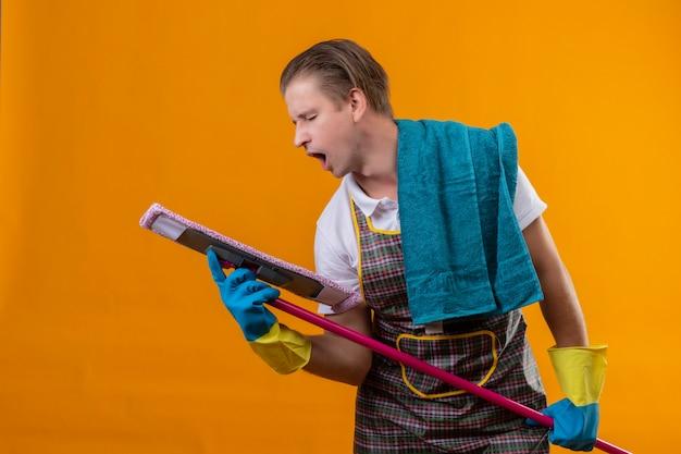 Jonge hansdome-mens die schort en rubberhandschoenen draagt die zwabber houdt die het als microfoon gebruikt