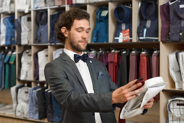 Jonge hansome donkerbruine mens die punt in boutique kiezen.