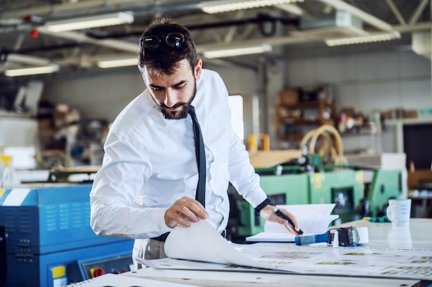 Jonge hardwerkende blanke bebaarde controller kijkt naar bedrukte vellen en evalueert de kwaliteit terwijl hij in de drukkerij staat.
