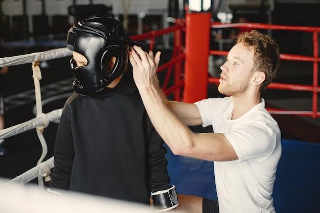 Jonge hardwerkende bokser die leert om te boksen. kind bij sportcentrum. kind dat een nieuwe hobby begint