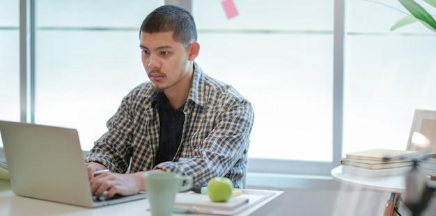 Jonge hardwerkende ontwerper die aan zijn project werkt