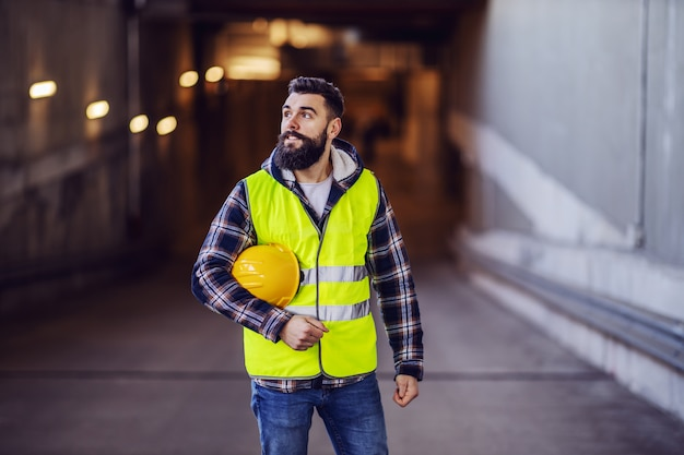 Jonge hardwerkende positieve bebaarde bouwvakker in vest veiligheidshelm onder oksel houden en opzoeken. bouwplaats buitenkant.
