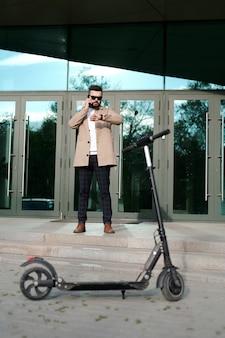Jonge hedendaagse zakenman die een afspraak maakt op de mobiele telefoon terwijl hij op de trap bij de ingang van het zakencentrum staat