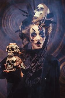 Jonge heks hloding schedel. lichte make-up en rook-halloween-thema. studio opname.