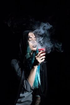 Jonge heks in kap die karmozijnrood rokerige drinkbeker houdt