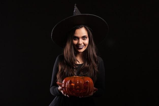 Jonge heks met een grote hoed die een enge pumpking vasthoudt. mooie jonge vrouw in een halloween-kostuum. fancy kostuum voor halloween.