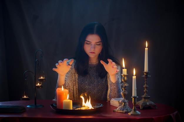 Jonge heks met vuur en brandende kaarsen op donkere achtergrond